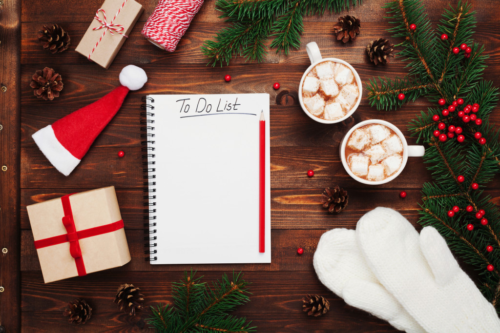 Two cups of hot cocoa or chocolate with marshmallow, gifts, mittens, christmas fir tree and notebook with to do list on wooden rustic background from above. Flat lay style.